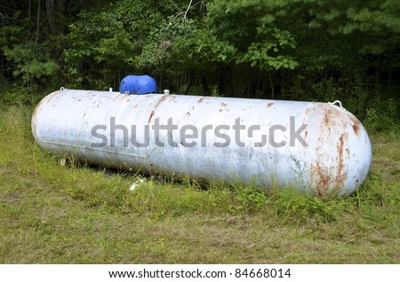 Rusting, old, painted propane tank - stock photo