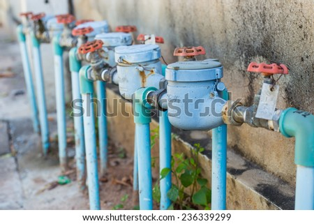 Rusting old water valve with water meter and old wall - stock photo
