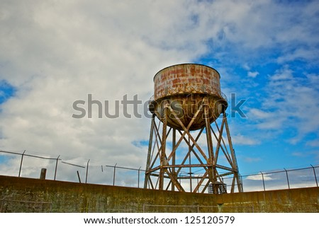 Rusting water tower stands above the the barbed wire wall of Alcatraz prison in San Francisco Bay. - stock photo
