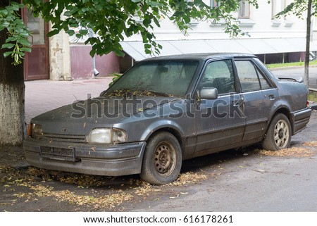 rusty abandoned car on a city street