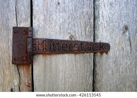 Rusty aged iron hinge weathered gray wood door                  - stock photo