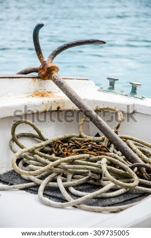 rusty anchor on the boat - stock photo
