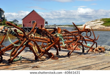 Rusty anchors on wharf at scenic fishing village of Peggy's Cove, Nova Scotia - stock photo