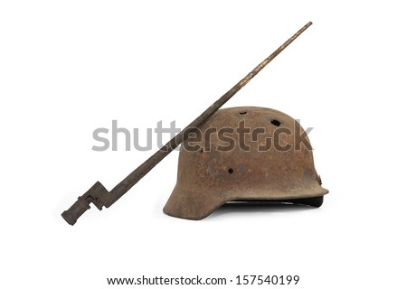 Rusty and holed German military helmet and Russian bayonet on white background