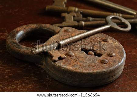 Rusty antique padlock with skeleton keys on a vintage wooden table. Macro still-life with side lighting to emphasize texture.  Shallow dof. - stock photo