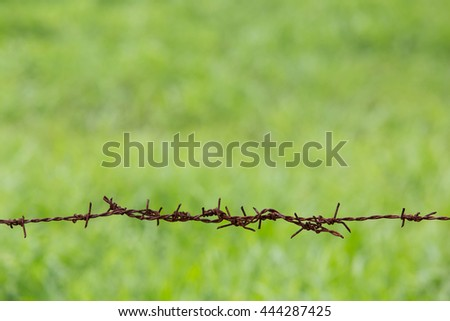 rusty barb wire fence - stock photo