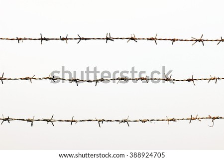Rusty barbed wire detention center isolated on white - stock photo