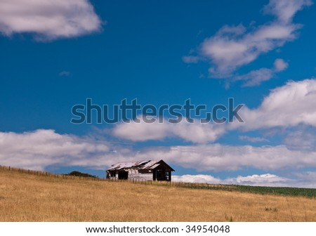 Rusty barn sits alone in a field in Hawkes Bay, NZ - stock photo