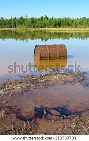 Rusty barrel and traces of the poured oil in the lake - stock photo