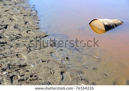 Rusty Barrel Pollutes River - stock photo