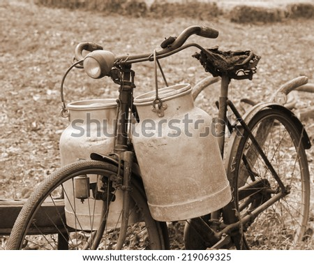 Rusty bike of a milkman of the last century with the bins for the delivery of fresh milk - stock photo