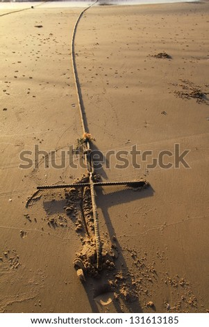 Rusty boats anchor solid in the sand on the coast - stock photo