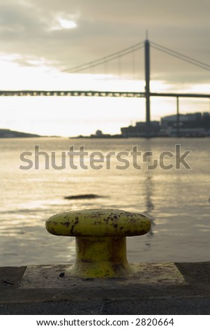 Rusty bollard at inlet with suspension bridge.