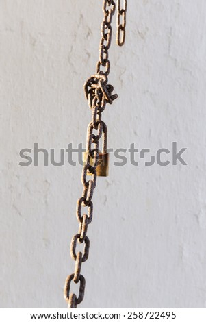 rusty chain and lock  hanging in front on a white wall - stock photo