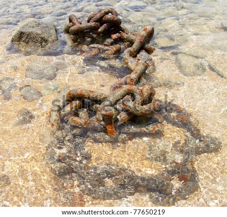 Rusty chain boats anchor solid in the sand on the coast - stock photo
