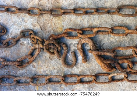 rusty chain with hook over stone background