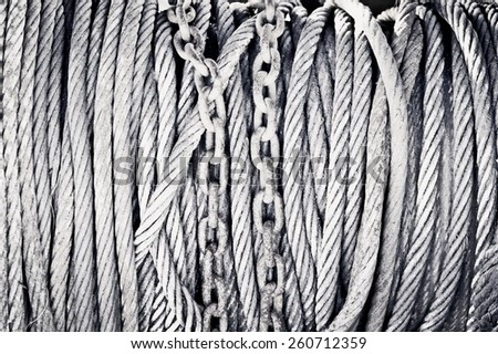 Rusty chains and wire cables as a background image in black and white - stock photo