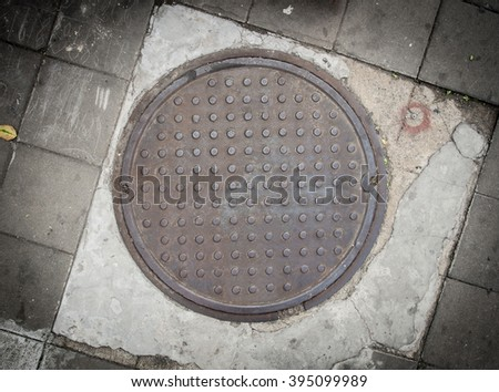 Rusty circle iron manhole cover on the concrete floor - stock photo
