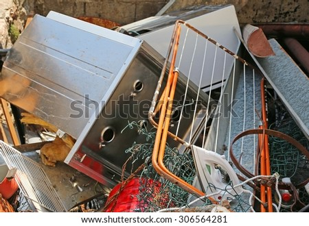 rusty clothes dryer and stove destroyed in ferrous waste dump - stock photo
