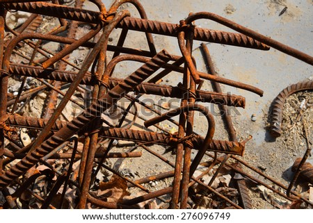 Rusty corroded stained metal pieces: wire, fitting, armature on a dirty concrete floor - stock photo