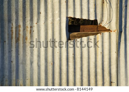 Rusty corrugated metal with a late-day shadow and a ragged hole.