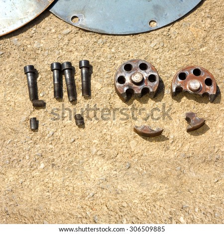 Rusty damaged disks, nut and bolts on the pavement - stock photo