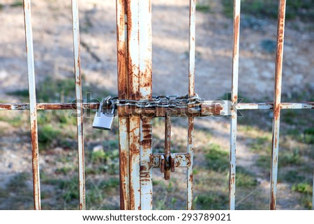 Rusty door with chain and padlock closed - stock photo