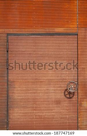 Rusty door with handle in shape of a wheel - stock photo