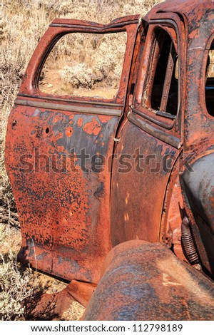 Rusty doors with just a bit of glass left in the rear door window and bullet holes here and there on this vintage vehicle - stock photo