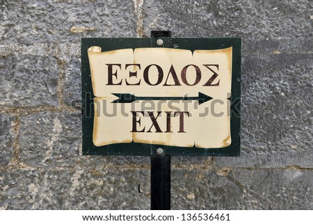 Rusty exit sign writed in english and greek - stock photo