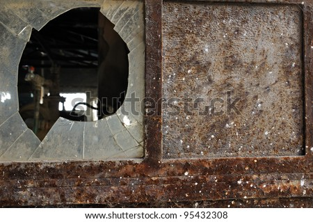 Rusty factory door and smashed glass. Industrial grunge background texture. - stock photo