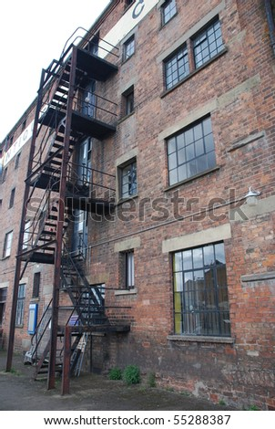 rusty fire escape stairs in a old brick wall building - stock photo