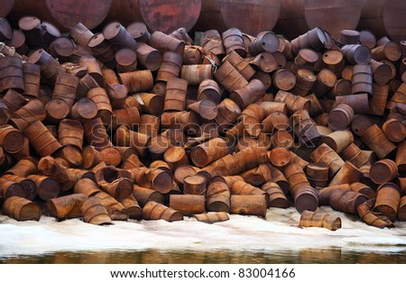 Rusty fuel and chemical drums on Arctic coast - stock photo