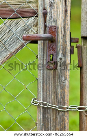 Rusty garden door with chain - stock photo