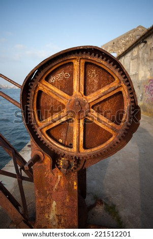 Rusty gear of a crane at river waterfront. - stock photo
