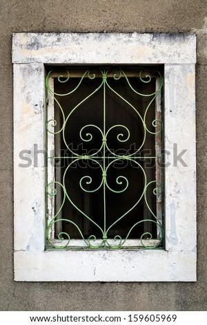 Rusty green metal window with decorative bars - stock photo