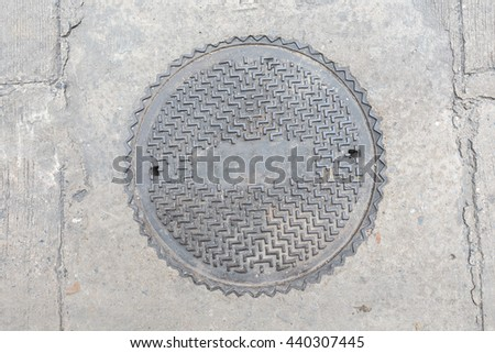 Rusty, grunge manhole cover in original background - stock photo