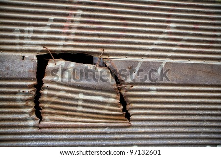 Rusty hole in sheet metal - stock photo