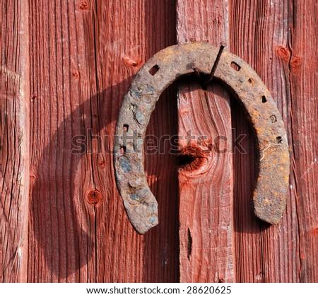 rusty horse shoe on a barn wall - stock photo