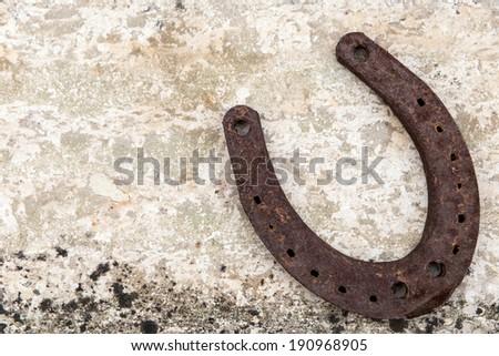 rusty Horseshoe on limestone as a lucky charm - stock photo