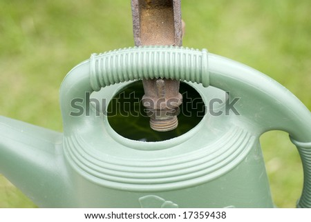 Rusty hose in green water container - stock photo
