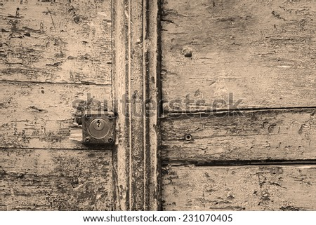 Rusty keyhole in a wooden door. Processed for sepia tone effect - stock photo