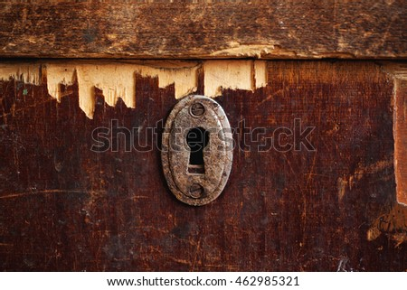 Rusty keyhole in old wooden wardrobe, closeup. selective focus