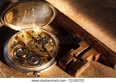 Rusty keys and an antique pocket watch on a grunge background