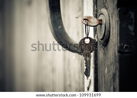rusty keys in old door lock - stock photo