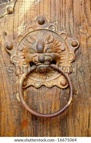 rusty lion/dragon head on Chinese traditional wood door.