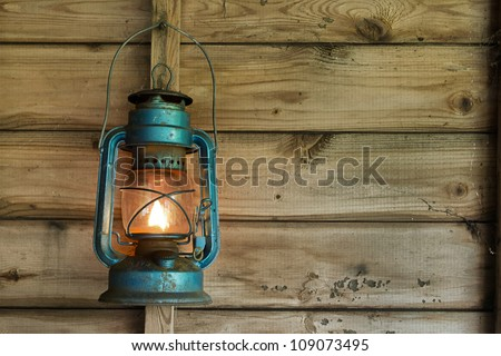 Rusty lit blue lantern hanging in an old shed - stock photo