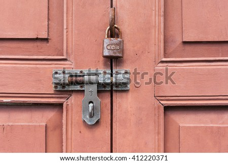 Rusty lock and bolts on red wooden door - stock photo