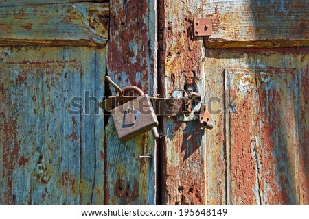 Rusty lock on old vintage rural wooden gate - stock photo