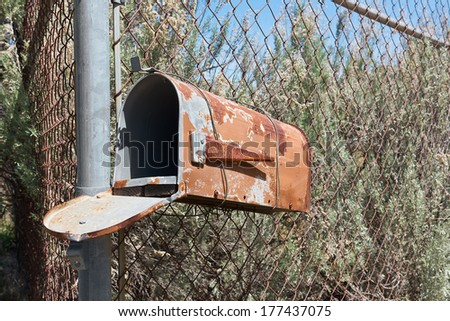 Rusty mailbox hangs off a metal fence.  - stock photo